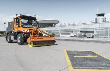 Unimog mit Kehrmaschine auf Flughafen